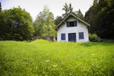 white cabin or barn with blue windows and door in green meadow. low point of view. Stock fotó