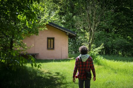 young man walking in a green meadow towards a pink cottage in the woods
