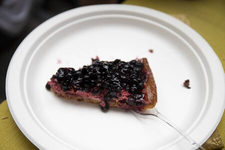 Slice of blueberry cake in a white disposable plate with a plastic fork. Rassa blueberry festival, Piedmont, Italy.