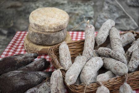 artisan cheese and sausages, typical italian products, exposed on a table at a local farmers market.