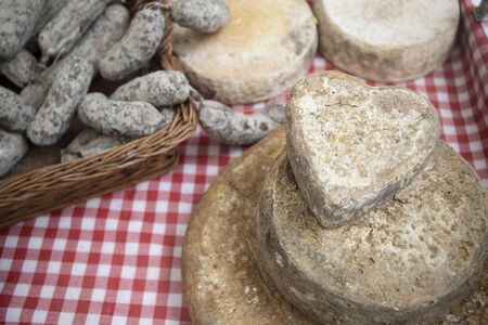 artisan heart cheese and sausages, typical italian products, exposed on a table at a local farmers market.