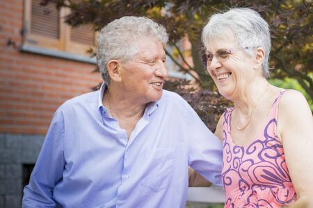 Portrait of an old couple, smiling at each other in outdoor scenery