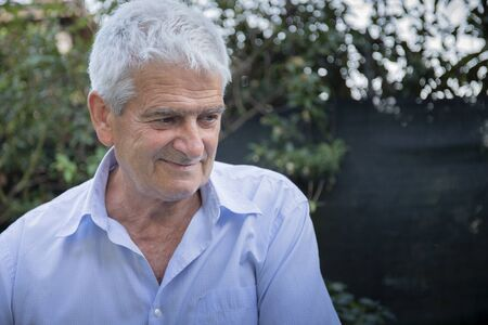 Older white man with grey hair, wearing a shirt, smiling and looking away in outdoor location with natural light.