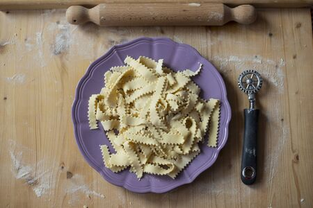 Raw homemade fresh pasta on purple plate before cooking, with cutting wheel and rolling pin Reklamní fotografie