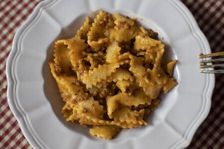 Top down close up of a plate of homemade pasta with meat sauce (rag?) and a fork.