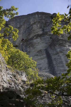 The vertical walls of the stone of Bismantova with two climbers. Vertical shot.