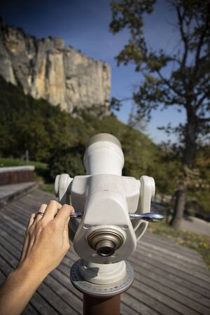 Touristic telescope with hand  pointing the vertical walls of the stone of Bismantova. Vertical shot.