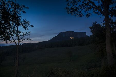 The stone of Bismantova, an isolated impressive spur in the italian appenines region. Blue hour, twilight view, framed by trees.