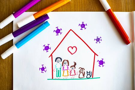 Little child's drawing, on wooden background with color pens around, representing she and her family and pets happy at home during covid-19 lockdown for coronavirus pandemic, with viruses outside of their house. Standard-Bild