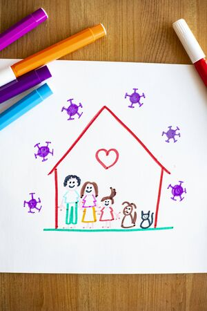 Little child's drawing, on wooden background with color pens around, representing she and her family and pets happy at home during covid-19 lockdown for coronavirus pandemic, with viruses outside of their house. Vertical shot.