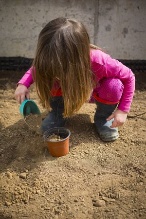 Little caucasian child girl, in her garden, filling a pot with a scoop during covid-19 lockdown. Outdoor idea activity for children at home in pandemic restrictions. Vertical shot.