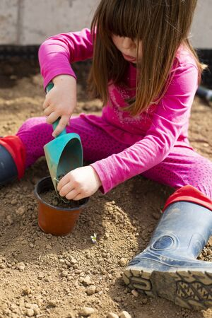 Little caucasian child girl, sitting in her garden, planting a plant in a pot with a scoop during covid-19 lockdown. Outdoor idea activity for children at home in pandemic restrictions. Vertical shot.