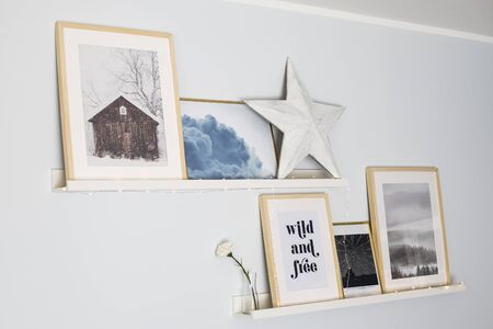 Wall shelves styled with a composition of prints, a wooden star and string lights. Home decor idea.
