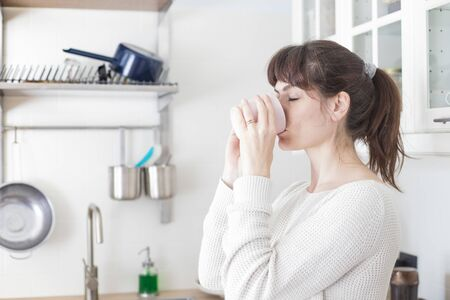 Pretty caucasian woman, with bangs and ponytail, drinking a cup of coffee in the morning in a white, bright lit, kitchen. Profile portrait, eyes closed.