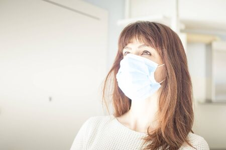 Caucasian attractive woman with long hair and bangs, wearing surgical blue face mask during covid-19 or coronavirus pandemic. Copy space on the left. 版權商用圖片