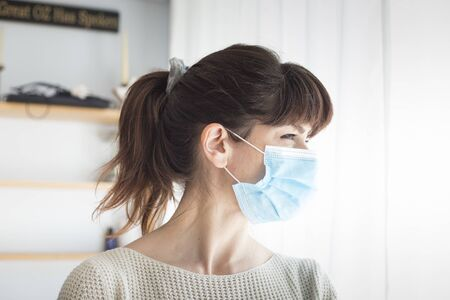 Caucasian attractive woman with ponytail and bangs, wearing surgical blue face mask during covid-19 or coronavirus pandemic. Profile portrait.