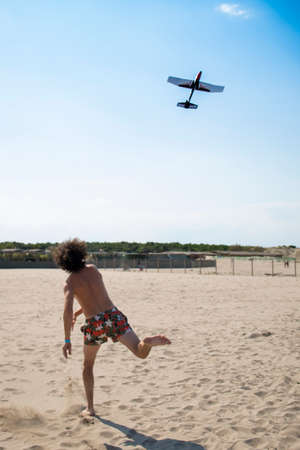 Young man, wearing a swimsuit, throwing a toy plane or glider on the beach in summer. Background or wallpaper with copyspace. Vertical shot. Rosolina mare, Veneto, Italy.