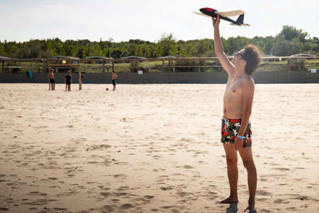 Young man, wearing a swimsuit, throwing a toy plane or glider on the beach in summer. Background or wallpaper with copyspace. Rosolina mare, Veneto, Italy.