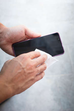 Male hands wiping smartphone screen with a white cloth. Vertical shot.