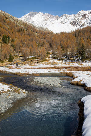 Man hiking near the river Duino, in the Preda Rossa Valley scenery in late autumn, with the first snow on a sunny day. Val Masino, Lombardy, Italy. Vertical shot.