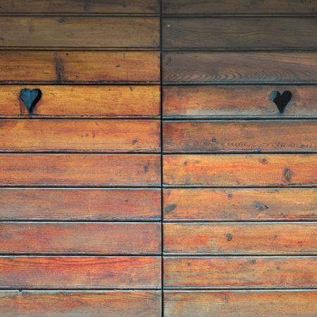 Detail of a wooden door with heart decorations photo