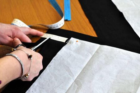 A sewing professional tailor at work making cloth