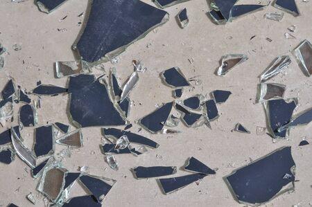 Broken mirror glass shards spread on the floor