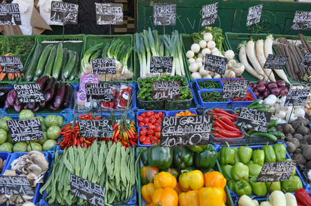 Fruits and vegetables at small grocery store produce market greengrocer with German labels with names of vegetables for sale