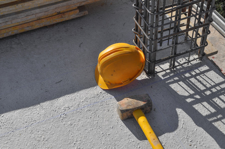 reinforcing: Reinforcing bar aka reinforcing steel or rebar for reinforced concrete structure and a hammer and safety helmet Stock Photo