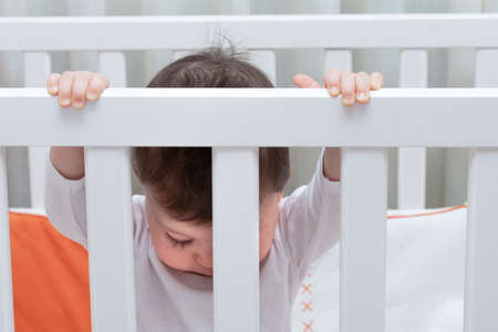 baby inside a white cradle holding the bars and looking down
