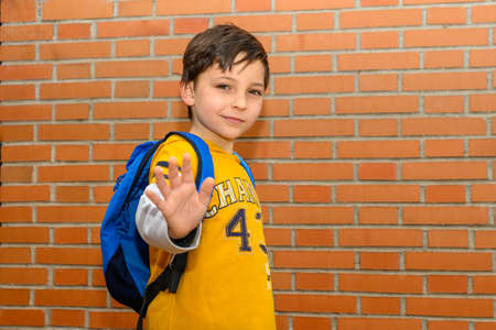 portrait of a child waving hello or goodbye. The boy is wearing a yellow T-shirt and a blue backpack in front of a brick wall. Standard-Bild