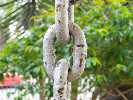 Close up of rusty chain links in foreground, with green on background Stock Photo