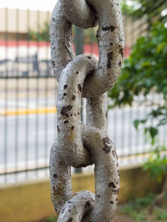 Close up of rusty chain links in foreground, with grid on background Stock Photo