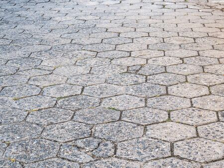 Street perspective texture of hexagonal concrete blocks, poorly maintained and deteriorated. Reklamní fotografie