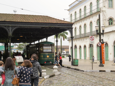 July 22, 2018, Santos, Sao Paulo, Brazil, former train station, in front of the Pel? Museum. Tourists boarding the electric tram for a rainy day tour.