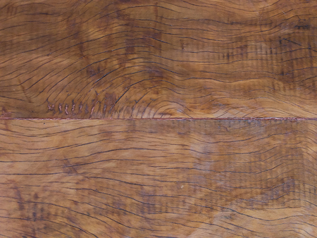 Close-up of old wooden floor with scratches and scorched marks.