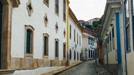 March 25, 2016, historic city of Ouro Preto, Minas Gerais, Brazil, side view of stone pavement street with old houses and church.