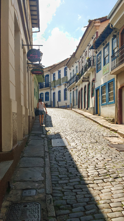 March 25, 2016, historic city of Ouro Preto, Minas Gerais, Brazil, side view of stone street with old houses in perspective and tourist strolling in the shade.