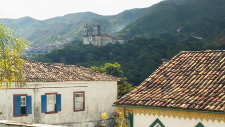 March 25, 2016, historic city of Ouro Preto, Minas Gerais, Brazil, World Heritage, rooftop view of colonial houses with ancient church in the background.