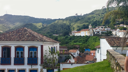 March 25, 2016, historic city of Ouro Preto, Minas Gerais, Brazil, World Heritage, rooftop view of colonial houses with ancient church in the background Editorial