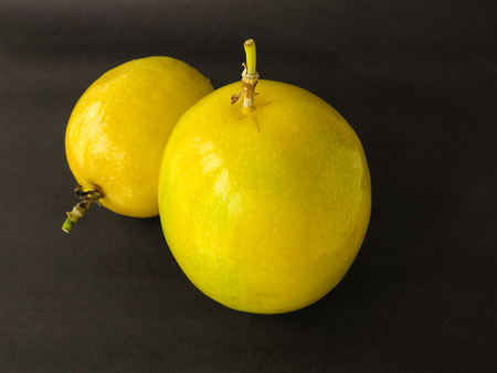 Two units of passion fruit, ripe, isolated on black background.