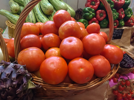 Basket of tomatoes and vegetable ingredients on the market.
