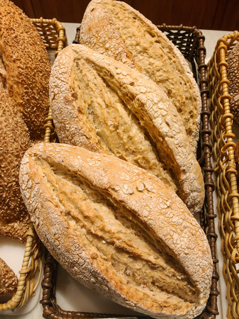 Basket of delicious baguette breads, with a view from above. With crisp bark details.
