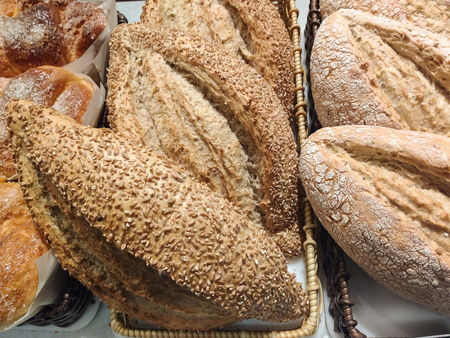 Baskets of bread with crusty bark, of grains, exposed in bakery. Banco de Imagens