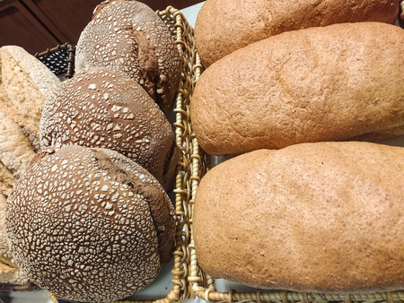 Baskets of breads of various types, with crusty bark, of grains, exposed in bakery.