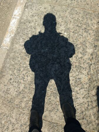 Shadow in silhouette of man standing in sunny day on rustic floor.