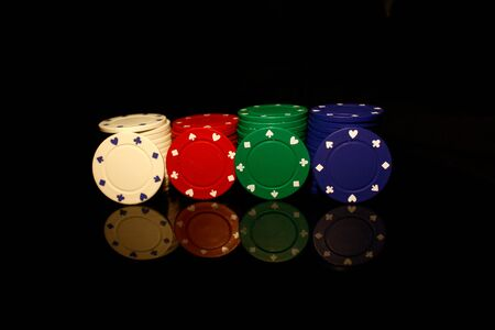 White, red, green, blue pocker chips stack with four  chips in front isolated on black with reflection