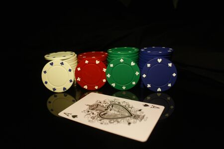 White, red, green, blue pocker chips stack with four  chips and an ace card in front isolated on black with reflection