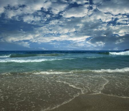 Dramatic beach landscape. Seascape, waves and clouds.
