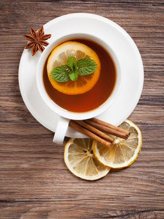 Mint tea with lemon and cinnamon on wooden background photo